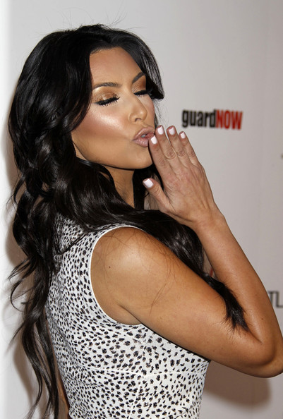 Kim Kardashian blowing a kiss with her fresh white nails